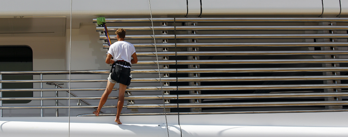Yacht deckhand cleaning a luxury yacht